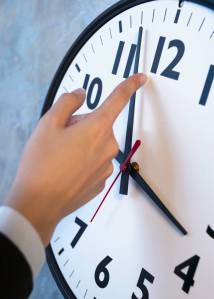 Finger turning back minute hand on a clock.