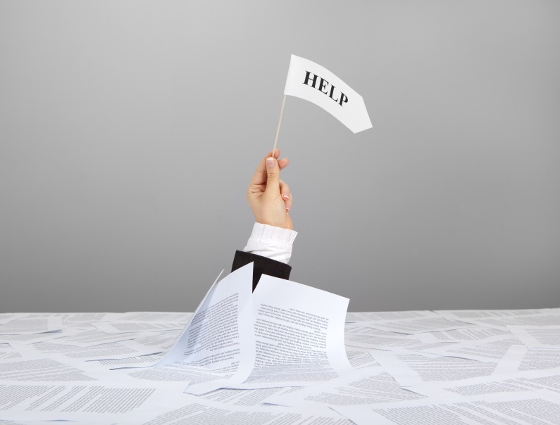 "Arm reaching up from a pile pf papers holding a white flag with the word ""Help"" on it."