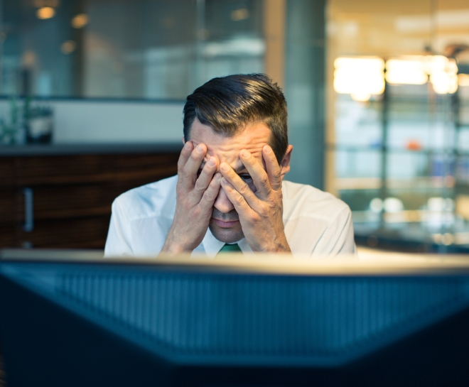 Man holding head in frustration in front of a computer