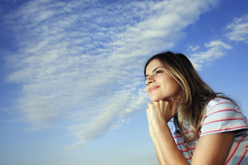 """Woman doing """"the Thinker"""" in front of a blue sky."""