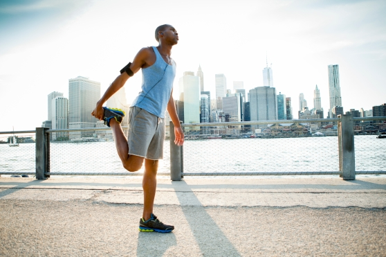 Man stretching before a run along a river in a city.