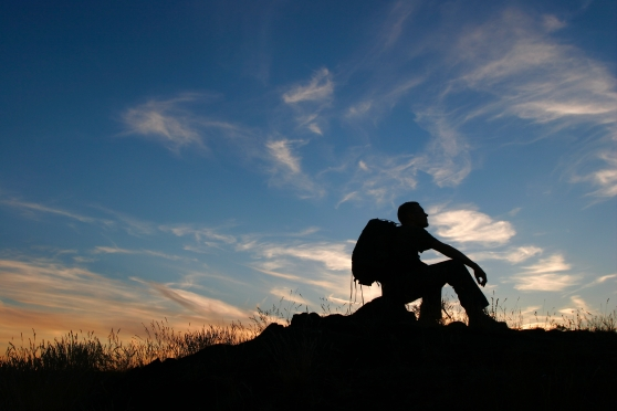 Silhouette of a man sitting with a hiking backpack beneath a sunset.