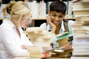 Two smiling people sitting at table, looking down at a pile of books.