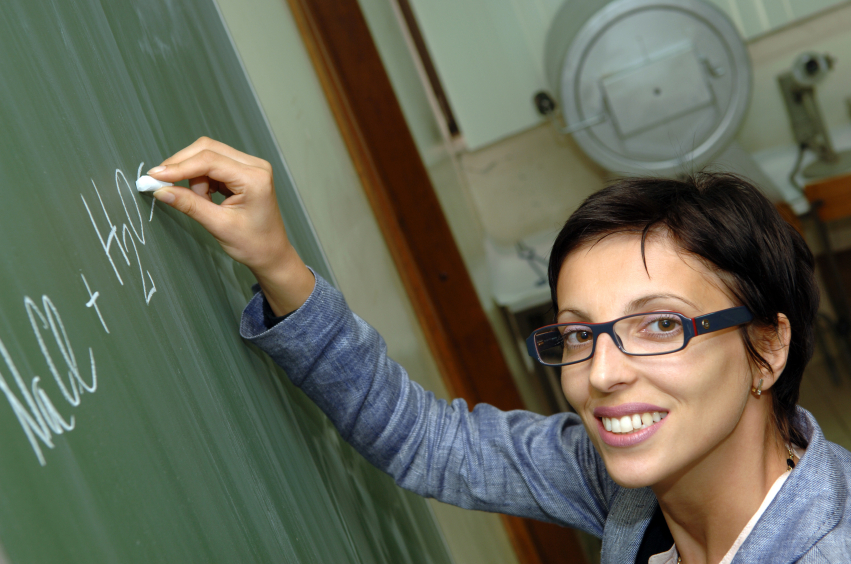 Woman writing chemistry formula on chalkboard.
